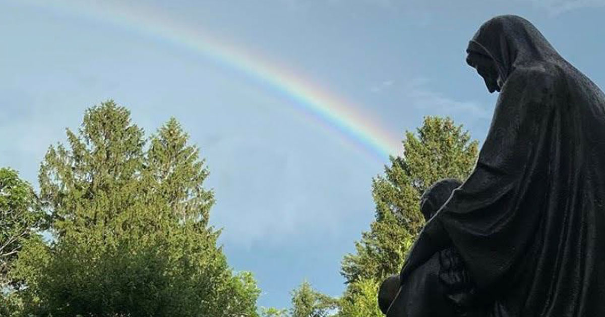 rainbow in the sky in front of marist statue